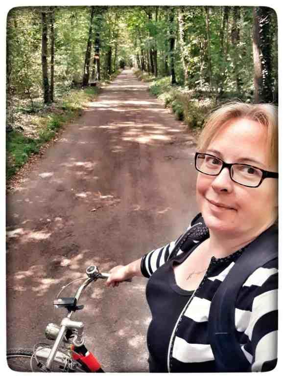 Fahrradweg an der Wiese durch den Wald
