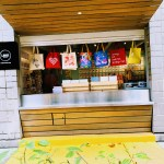 Window into SJMade store showing off their shopping totes.
