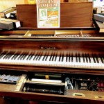 Electric piano with rolls of music and a poster for Golden Summertime.