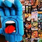 A giant blue foam hand with a tongue sticking out in front of speed wheel posters.