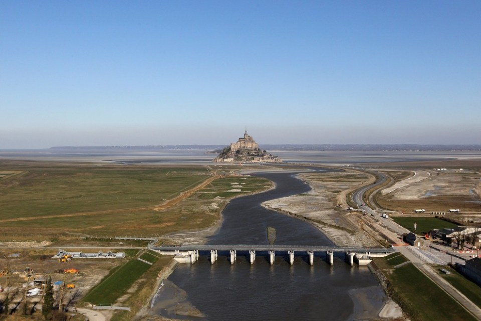 An aerial picture taken on February 2, 2012 shows the Mont-Saint-Michel, a tourist attraction and Unesco world heritage site in northwestern France. At the foreground, the hydraulic dam built in 2009 as part of a project aimed at making the Mont-Saint-Michel an island again. The dam uses the waters of the river Couesnon and of tides to help remove the accumulated silt deposited by the rising tides. The project also included the destruction of the causeway that had been built on top of the small land bridge and enlarged to join the island to the continent, and was used also as a parking lot for visitors. It will be replaced by an elevated light bridge. AFP PHOTO/KENZO TRIBOUILLARD