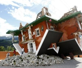 People walk out of a house, which was built upside down by Polish architects Irek Glowacki and Marek Rozanski, in the western Austrian village of Terfens May 5, 2012. The project is meant to serve as a new tourist attraction in the area, and is now open for public viewing. Picture taken May 5, 2012. REUTERS/Dominic Ebenbichler