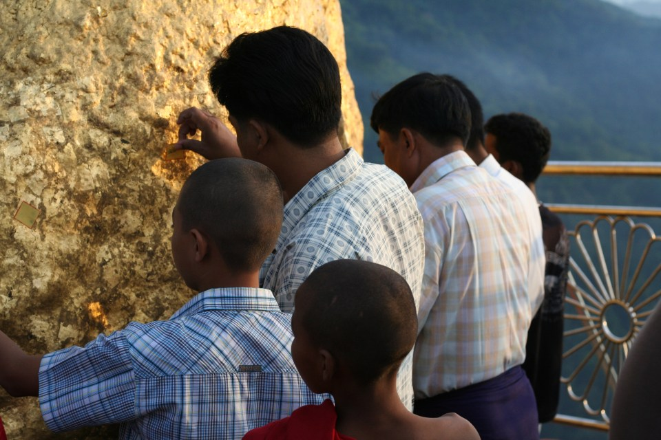 Putting Gold Leaf on the rock as an offering  Image Credit Flickr User Pyjama
