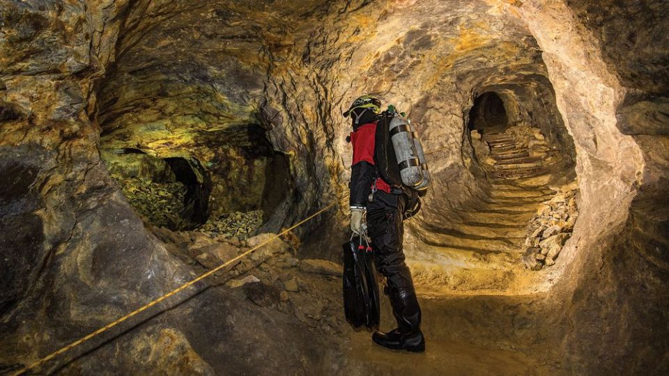 Divers descend muddy stairs to ­access ­flooded tunnels