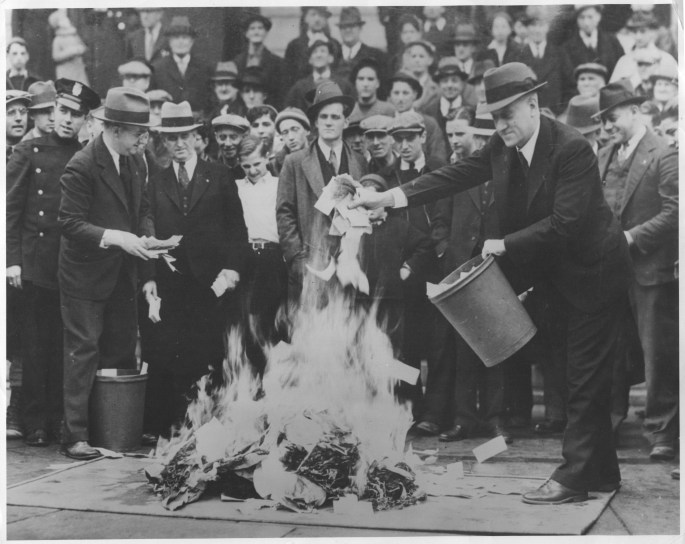 """Crowds gather as hundreds of thousands of dollars in """"Scrip Money"""" are burned.  The notes were issued after the bank had closed.  April, 1933. 306-NT-177.567C"""