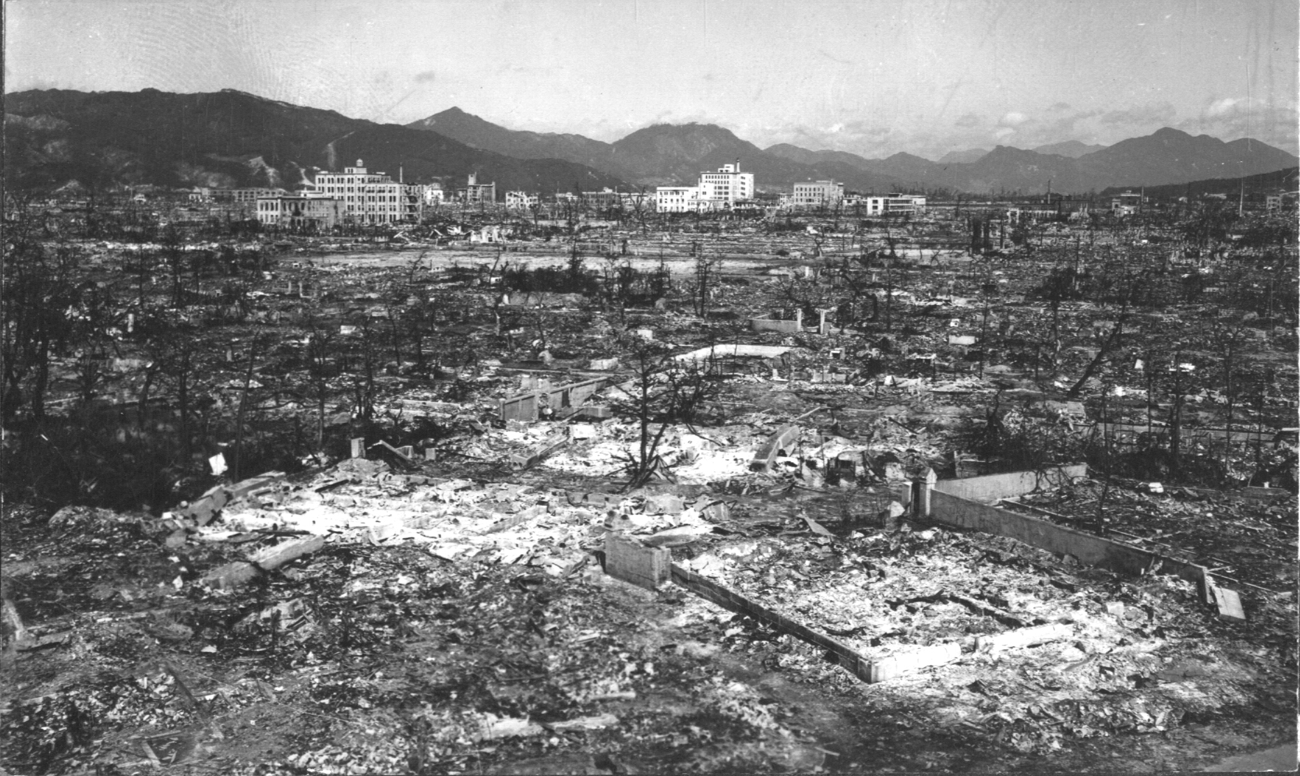 Photograph of Hiroshima after atomic bomb. Buildings have been reduced to rubble. Mountains are in background.