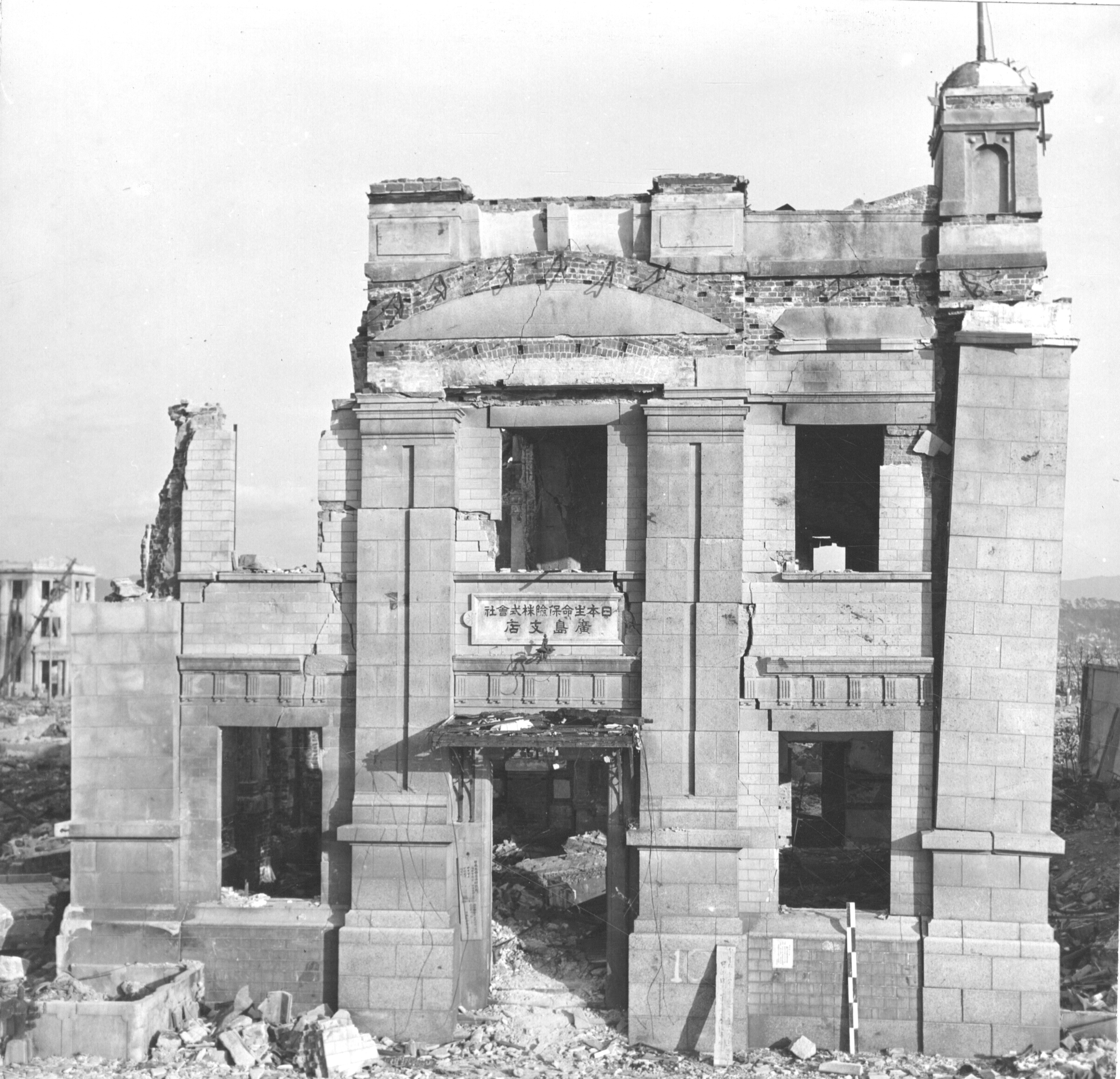 Photograph of Hiroshim after the atomic bomb. A stone building stands windowless, surrounded by rubble.