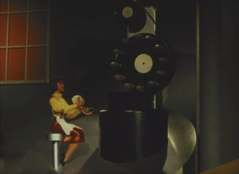 In a confusing tableau, a woman applies face powder while operating machinery.