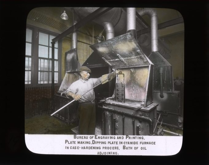 Bureau of Engraving and Printing. Plate making. Dipping plate in cyanide furnace in case-hardening process. Bath of oil adjoining. RG 56-AE-19.