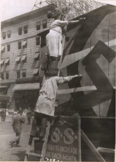Women Camouflaging the War Savings Stamps Booth at Broadway and 43rd Street, New York. Local ID: 165-WW-599G-41.