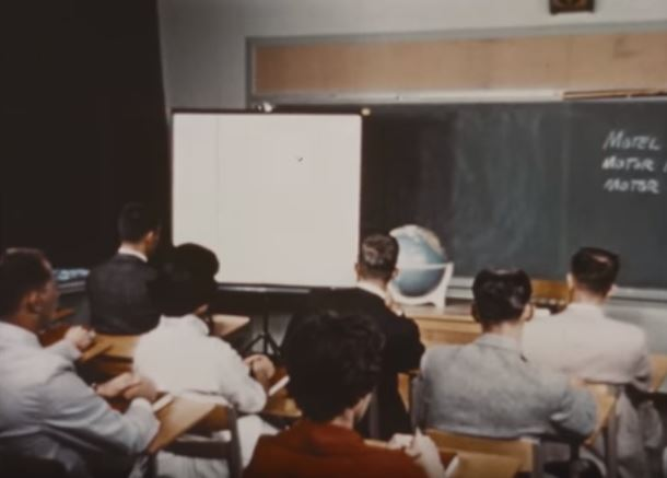 """Still from """"Small Town Espionage"""" (263.3153). Students wait for the lights to dim before a classroom movie."""