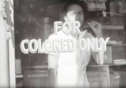 """A woman stands in the window of a segregated restaurant. Still from outtakes from """"Dixie, U.S.A"""""""