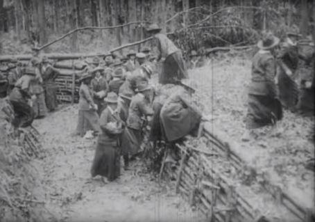 Women traverse a trench.