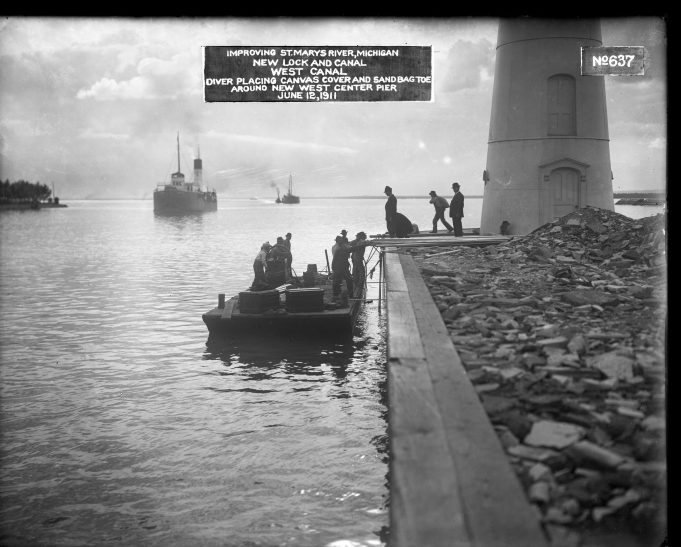 """Workmen standing on a flat boat of some kind next to a pier on which the bottom of a lighthouse structure is seen. Two men in bowler hats stand on the pier while a worker in the background carries a sack over his shoulder. Two ships are seen in the distant background. Label on the original photograph reads, """"Improving St. Marys River, Michigan. New lock and canal. West Canal. Diver placing canvas cover and sandbag toe around new West Center Pier. June 12, 1911."""