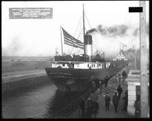 """Great Lakes bulk carrier ship """"Richard Trimble"""" making the first down lockage in the new lock. Label on original photograph reads, """"Improving St. Marys River, Michigan. New lock and canal, Farrell and Trimble in 3rd lock making first down lockage, October 21, 1914."""""""