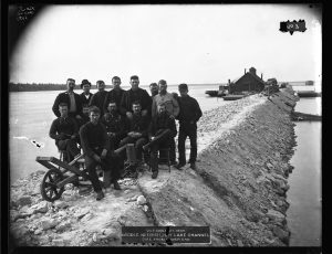 """Fourteen men pose for a group photograph while standing on a dike in the Hay Lake Channel. A label on the original photograph reads """"October 27, 1889. Middle Neebish, Hay Lake Channel. Dike from Lower End."""""""