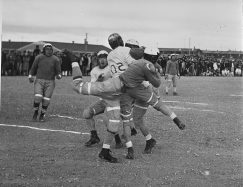 """Original Caption: Heart Mountain Relocation Center, Heart Mountain, Wyoming. An exciting bit of aciton between the """"All Stars"""" and """"Jack Rabbits"""" football teams, during a game at the Heart Mountain Relocation Center. At the moment it is difficult to say who has the ball. Local ID: 210-G-G211"""