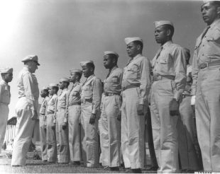 """""""The thirty smartly disciplined members of """"Squadron 10"""", first colored unit to report for navigation training at Hondo Army Air Field, Hondo, Texas, are shown being inspected shortly after their arrival at the huge navigation airbase. The inspecting officer is Captain Frank H. Sheffield. At his left is Navigation Cadet Arnold W. Galimers, flight marcher for the colored group. """" (342-AM-173976)"""