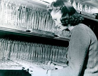 """""""Girl inspecting electric light bulb filaments."""" Date Taken: 1958 (Local ID: 174-G-55-1)"""