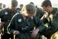 """""""PFC. Maureen Daugherty, the first U.S. military woman to make a parachute jump in Bolivia, straps on her gear during Fuerzas Unidas Bolivia, a joint U.S. and Bolivian training exercise."""" Date Taken: April 1986 (Local ID: 330-CFD-DF-ST-87-02152)"""