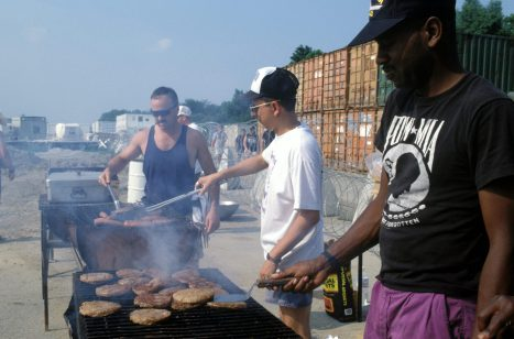"""(Local Identifier: 330-CFD-DF-ST-96-00272) """"Trading paper pushing for hamburger flipping, to the right of your screen, is DK1 Earl Jones, US Navy, as he cooks for the Independence Day cookout at Camp Pleso. For the camps security, concertina wire is seen in the background."""""""