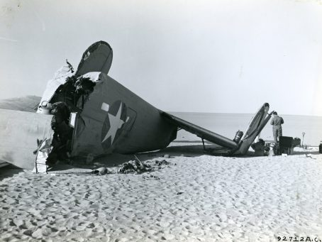 An investigation searches the nose of the B-24. The starboard main landing wheeel is in the foreground, still fully inflated. Above the wheel is the mounting of the No. 4 engine, which tore loose when the plane crashed. Local ID: 342-B-ND-075-4-92712AC