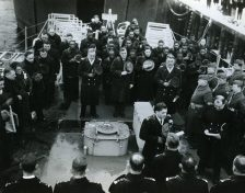 Lt. A. Boyd Turner at microphone. Ship's Chaplain on duty at the Yard, leads all 216 members of the ship's company and 300 guests in prayer. Date TakenL 20 March 1944. (Local Identifier: 80-G-218860)