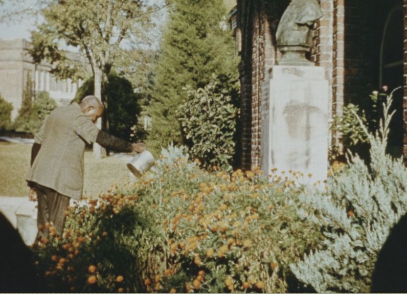 George Washington Carver waters flowers on the campus of Tuskegee Institute.