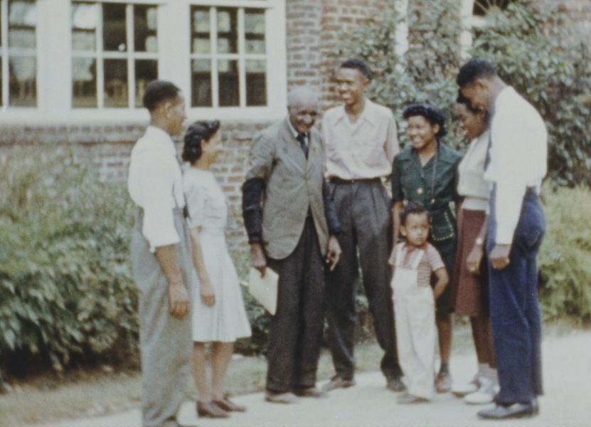 George Washington Carver surrounded by a group of people.