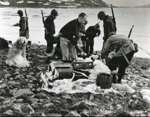 Original Caption: Destroy German radio base in Greenland. Members of the combined U.S. Coast Guard and Army task force examine an abandoned Nazi parachute kit found on the site of the German Army's radio base. Food, hand grenades, and other material where abandoned by the Nazis following the attack on the base by an American Army Air Force. The Germans presumably were excavated by plane. Local Identifier: 26-G-09-21-43-7 (Box44)
