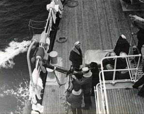 Original Caption: Coast Guard in Greenland. Coast Guard gun crews are shown as their ship heads out for patrol in the shipping lanes off the coast of Greenland. Local Identifier: 26-G-10-17-42-2 (Box 44)