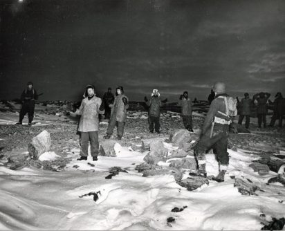 Original Caption: Coast Guardsmen surprise and capture 12 Nazis on last Greenland weather base. Landing under the cover of darkness, Coast Guardsmen from a combat cutter captured 12 at what is believed to be the last enemy radio-weather outpost in Greenland. Supplies were seized as the enemy surrendered without firing a shot. Later, a Nazi trawler with its crew of 20 was captured and salvaged in another surprise operation. Here, Coast Guardsmen keep alert guard over prisoners, whose hands raised in surrender. The picture was made by a Coast Guard combat photographer before dawn. Local Identifier: 26-G-2993 (Box 45)