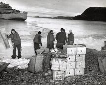 Original Caption: Coast Guard turns over captured German supplies to Danish sled patrol. Somewhere along the rugged northeast coast of Greenland, Coast Guardsmen deliver supplies captured in a surprise raid on a Nazi radio-weathers station to the Danish Sled Patrol. Twelve Germans fell prisoners of war without resistance in the pre-daylight action. Later, two Coast Guard combat cutters took a German trawler, beset in the Ice Pack, before its crew could destroy it. Salvoes from Coast Guard guns brought a quick surrender from the Nazi ship. Local Identifier: 26-G-2998 (Box 45)