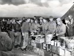 """Photo ID: 111-SC-164149. Original caption: """"Christmas Day dinner in North Africa. They had turkey, cigarettes, oranges, and candy."""" Photo by: Youkes Les Baines of the 49th Fighter Squadron. Date: December 25th, 1942"""