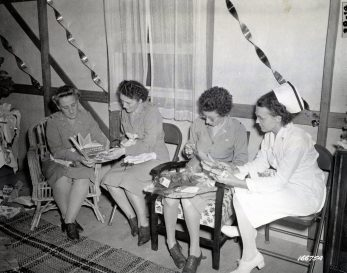 """Photo ID: 111-SC-166754. Original caption: """"Lt. Irene Williams (Milwaukee, Wisconsin); Kathereen O'Doherty (San Antonio, Texas); Edith Rose (Prince Edward Island, Canada); and Opal Coffey (Humeston, Iowa) compare gifts received at the Christmas Eve gathering of nurses and officers at a hospital in Australia."""" Photo by: 172nd Station Hospital, Indooroopilly, Australia. Date: December 25th, 1942"""