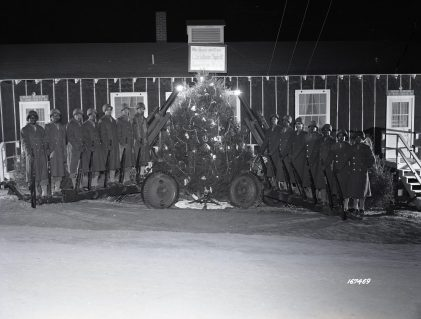 """Photo ID: 111-SC-167469. Original caption: """"Christmas tree and Howitzers form the holiday theme of Battery C, 599th Field Artillery Battalion, Camp Joseph T. Robinson, Arkansas. """"We guarantee Christmas spirit American style."""" From left to right: Pvt. Lewis Cox, Pvt. Charles Dunnings, Cpl. Alfonso Swain, Pvt. Homer Lee Johnson, Pvt. Frank Black, Pvt. Alexander Jones, Sgt. Willie Wright, Pvt. Dumas E. Bennett, Pvt. Amos Smith, Pvt. Henry Bowman, Pvt. David Swayze, Pvt. John Coles, Pvt. Wesley Douglas, Sgt. Albert Sawyer."""" Date: December 1943"""