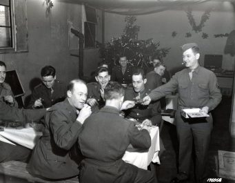 """Photo ID: 111-SC-176868. Original caption: """"Christmas day somewhere in England. Staff Sgt. William Steinbeck of New York, New York, passes out the cigars to the boys. Tomorrow though it might be K.P. [kitchen patrol/kitchen police], so watch out fellows....Men are members of Company C, 56th Signal Battalion, V Corps, stationed at Bristol, England."""" Date: December 24th, 1942"""