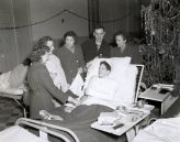 """Photo ID: 111-SC-199277. Original caption: """"WACS bring Christmas gifts to patients in American hospital in Paris. Left to right: Sgt. Helen Miller (Portland, Indiana); Pfc. Hubert Taylor (Glenmary, Tennessee); T5 Clara Ellen Humer (Danville, Illinois); Pvt. John W. Bonnell; and WAC Pft. Marion Olson (Houston, Minnesota). The patient in bed is Sgt. Charles Sipe (646 Homeplace Avenue, Indianapolis, Indiana)."""" Photo by: 48th General Hospital. Date: December 25th, 1944"""
