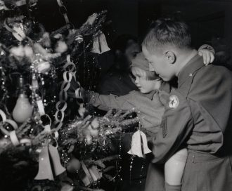 """Photo ID: 111-SC-356037. Original caption: """"Being only four, Donny F., orphaned by the Blitz, hasn't ever seen a Christmas tree decorated with an abundance of peacetime trinkets. But Cpl. James H. Enicks (801 East Water Street, Greenville, Ohio) did his best when he decorated this tree. Donny's smile when she saw it was reward enough. The occasion was an Christmas week party given by the staff of an American hospital in London."""" Photo by: Schillinger (16th Station Hospital, London). Date: December 24th, 1943"""