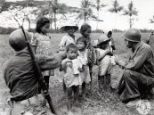 """Photo ID: 111-SC-377725. Original caption: """"Left to right: Pfc. Philip H. Dunbar (Worcester, Massachusetts) and Pvt. Si Gerson (New York City) giving Christmas candy to Filipino children in San Jose, Mindoro Island."""" Photographer"""" Pvt. Ben Gross. Date: December 25th, 1944"""
