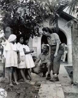 """Photo ID: 111-SC-377726. Original caption: """"Outside of the """"Church of Christian Endeavor"""" WAC Sgt. Nellie Ross and her brother, Pvt. Charles Ross, pause to wish Christmas greetings to three young Filipino children before going to services. This the first reunion for Nellie and Charles in over four years."""" Photographer: T4 Jack Pfieffer. Date: December 25th, 1944"""
