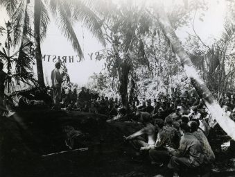 """Photo ID: 127-GW-1083-74819. Original caption: """"Merry Christmas is the title of Chaplain Rabun's sermon as he delivers it to the men of 1st Battalion, 9th Marines while standing under the sign Merry Christmas made by the 1st Battalion Marines. Bougainville."""" Photographer: Sgt. R. Robbins. Date: December 25th, 1943"""