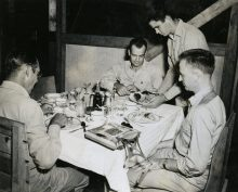 """Photo ID: 127-GW-908-73785. Original caption: """"Christmas dinner on Guadalcanal after returning from Bougainville Campaign. Lt. Comdr. Fred E. Bradford (Los Angeles, CA), Major William M. Gilliam, and Major Martin Fenton (Mt. Kisco, New York."""" Photographer: C.H. McClure. Date: December 25th, 1943"""