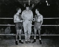"""Photo ID: 127-GW-928-69515. Original caption: """"Three champs in the So. Pac...Lt. Comdr. Gene Tunney (USNR) awards Pvt. Harvey Weiss (USMC, left) with the """"Betty Garble"""" medal and Pvt. Morris Weiss (USMC, right) with the """"Lana Turner"""" medal after they won their fights in the Armed Forces South Pacific Boxing Tournament. The Weiss boys are twin brothers and live at 1266 Holdstead Avenue, Bronx, New York. Guadalcanal, Solomon Island."""" Photographer: Cpl. Poole. Date: December 24th, 1943"""