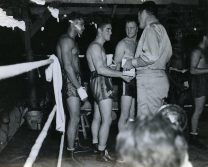 """Photo ID: 127-GW-928-69516. Original caption: """"Southern Pacific champs receive medals from ex-world champ: Receiving the """"Greer Garson"""" medal from Lt. Comdr. Gene Tunney (USNR) for winning the championship in the South Pacific Armed Forces Boxing Tournament is Pvt. R. O'Briend (USMC). Other winners shown in the picture are J. Jeffers (USN, left) and Dell Sparr (USN, between O'Brien and Tunney). Guadalcanal, Solomon Island."""" Photographer: Cpl. R.M. Cusack. Date; December 24th, 1943"""