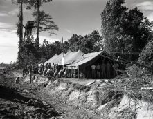 """Photo ID: 127-N-71432. Original caption: """"By the roadside...by the side of a jungle road at Empress Augusta Bay, Marines, sailors, and soldiers gather for Mass that fills the tent chapel to overflowing. Bougainville."""" Photographer: Sgt. W.G. Wilson. Date: December 25th, 1943"""