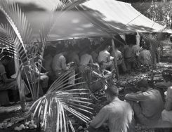 """Photo ID: 127-N-73805. Original caption: """"Marines listening to Chaplain Westwood preaching in and outside of the Chapel on Christmas morning. Guadalcanal."""" Photographer: Pfc. C.H. McClure. Date: December 25th, 1943"""