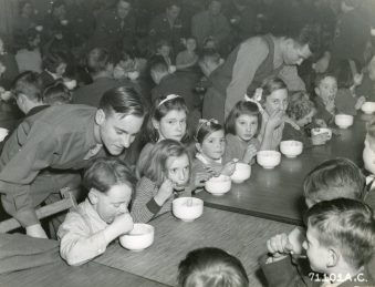 """Photo ID: 342-FH-3A-14616-71101AC. Original caption: """"On 23 December 1944 British youngsters were guests of honor at a Christmas party given by enlisted men of the 379th Bomb Group at their club on an 8th Air Force base in England."""" Date: December 23rd, 1944"""