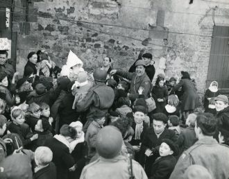 """Photo ID: 342-FH-3A-17858-70030AC. Original caption: """"Santa Clause made an appearance at a Christmas party given by the American Red Cross for French children at the 386th Bomb Group base in Beaumont, France."""" Date: December 25th, 1944"""