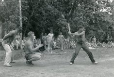 """Photo ID: 342-FH-3A-45193. Original caption: """"Christmas day baseball game 13th AAF vs 46th Signal Company. Umpire - Cpl. Will; Catcher - Pfc. Reuter; Batter - Cpl. Thuerer. War Theatre #23 - South Pacific."""" Date: December 25th, 1943"""